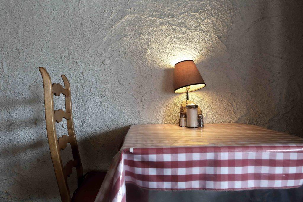 Vom genießen. Tisch mit rot-weiß-karierter Tischdecke, Stuhl und Lampe