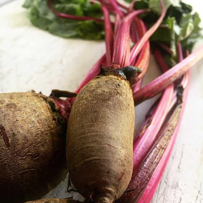 Veganes Rezept für Nudeln mit rote Bete Blättern und gerösteten Mandeln. Rote Bete mit Blättern auf weißem Holzuntergrund